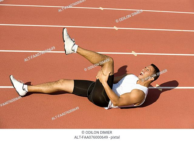 Injured runner lying on running track