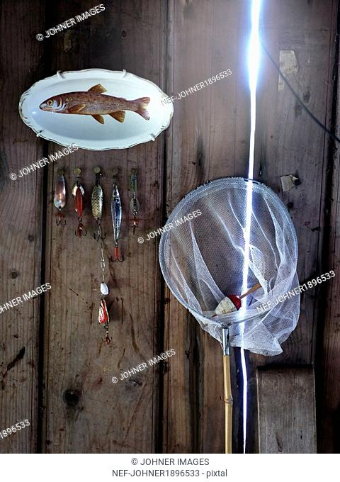 Bag net, floats and plate with illustration of fish on it, close-up