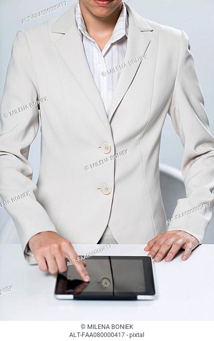 Businesswoman using touch screen on digital tablet