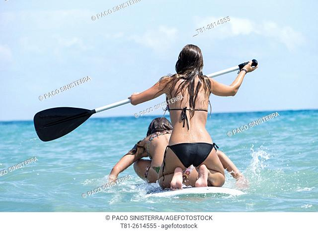 Young girls on paddleboard, Peñiscola, Spain