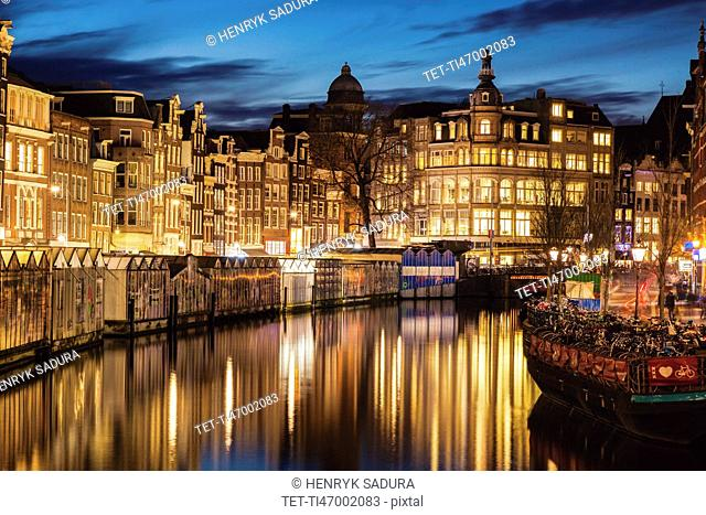 Netherlands, Amsterdam, Illuminated old town upon canal in Amsterdam