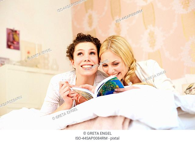 Women reading together in bedroom