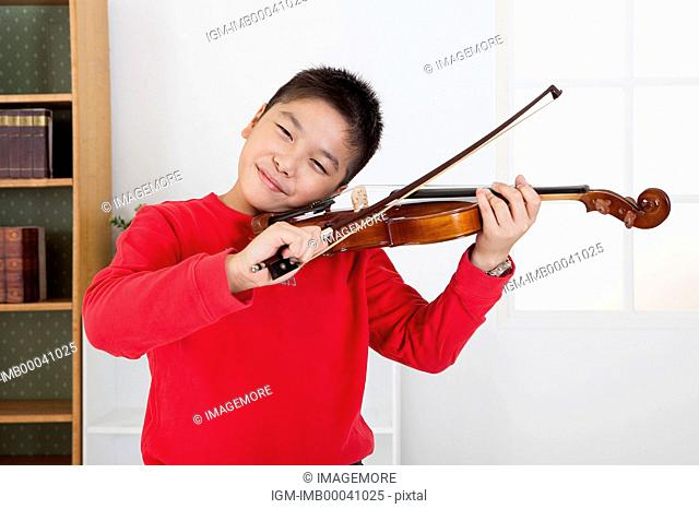 Boy playing violin with smile