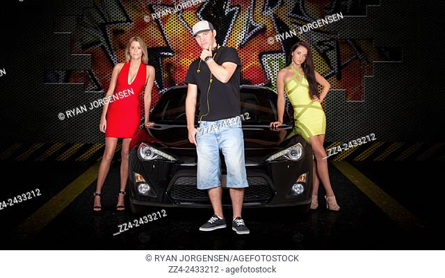 Group of young people posing beside black modern car in underground parking lot with graffiti background. Motoring enthusiasts (graffiti hand drawn