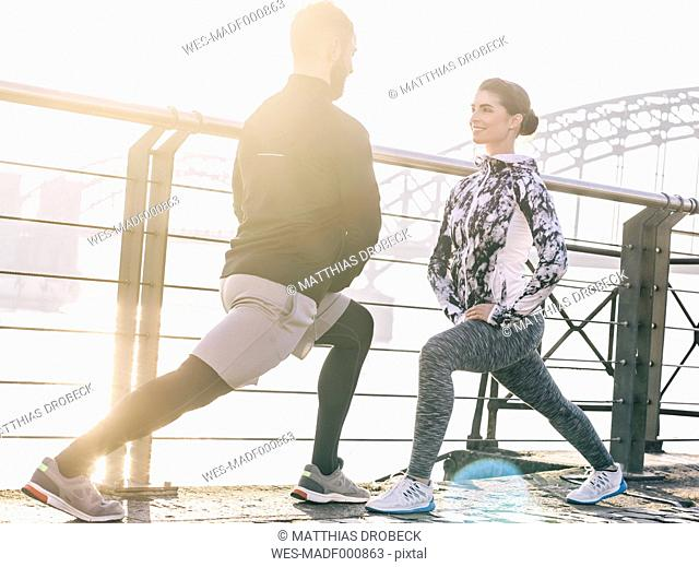 Germany, Cologne, Young couple worming up for workout, stretching