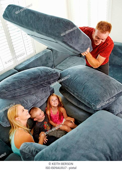 Father covering family sitting among cushions in living room