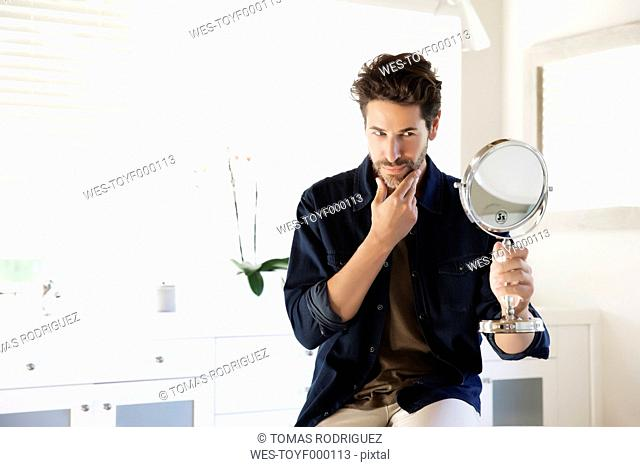 Man sitting in bathroom looking at mirror