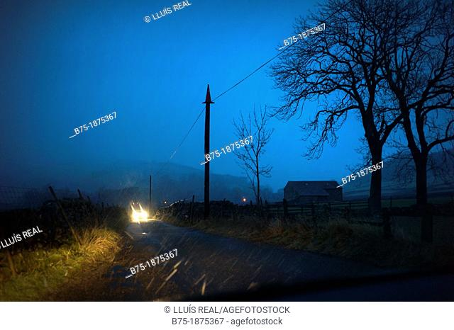 UK, England, North Yorkshire, Yorkshire Dales, country road, car headlights