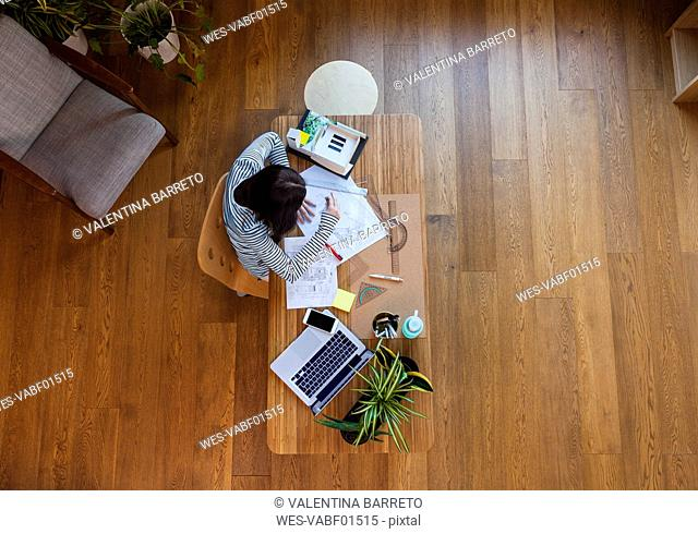 Young architect working in office, from directly above