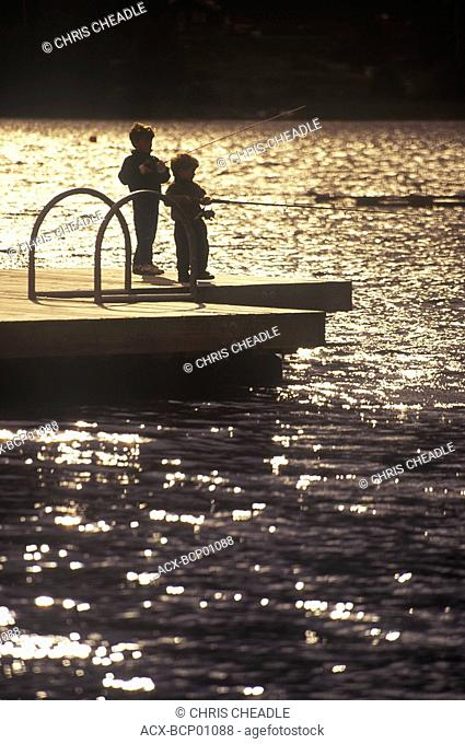 Two boys fish from floating dock by lakeside, British Columbia, Canada