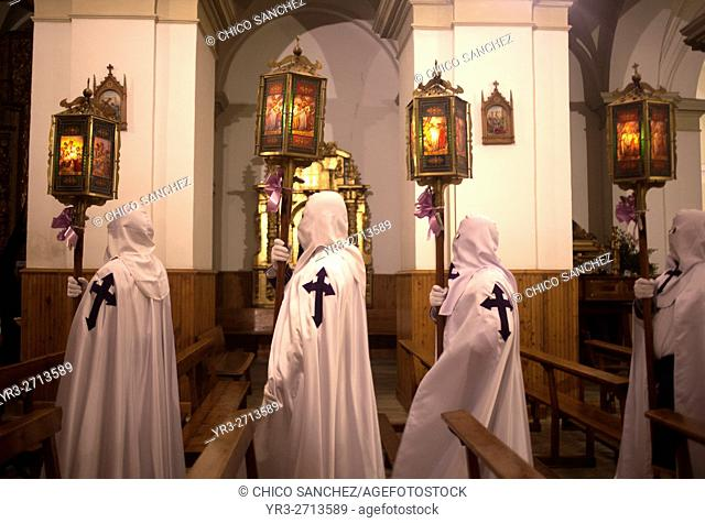 Hooded penitents wearing the cross of Saint James hold candles during an Easter Holy Week procession in Astorga, Castilla y Leon, Spain