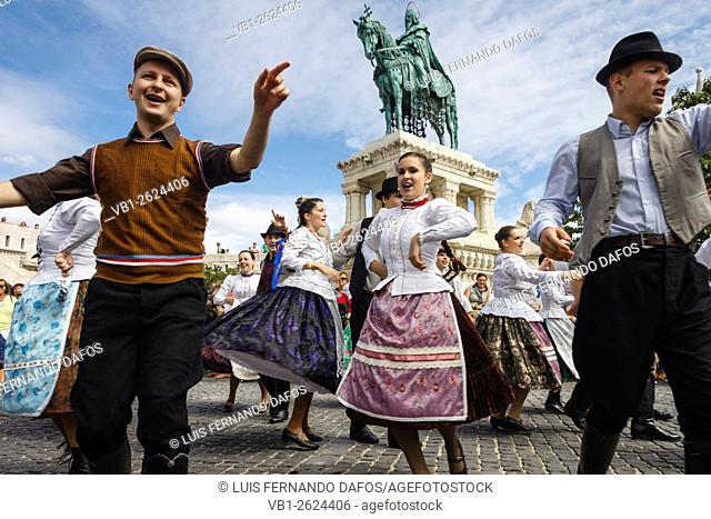 Dancing in traditional costumes by the equestrian monument to King Stephen I during the International Wine festival at Castle Hill, Budapest, Hungary