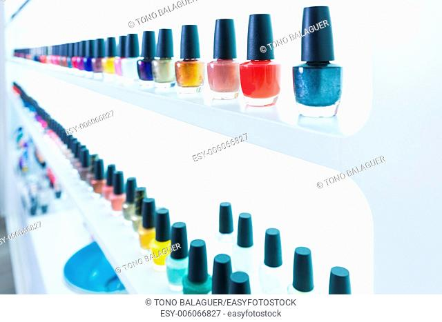 colorful nail polish colors in a row at nails saloon on white background