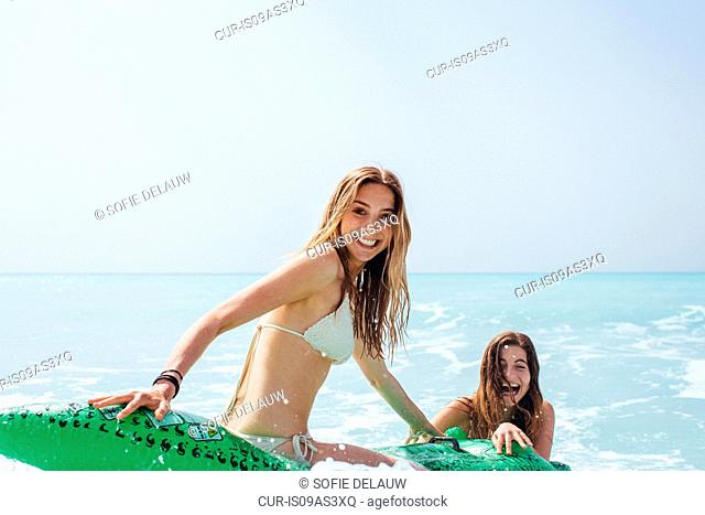 Portrait of two young female friends wearing bikinis playing on inflatable crocodile in sea