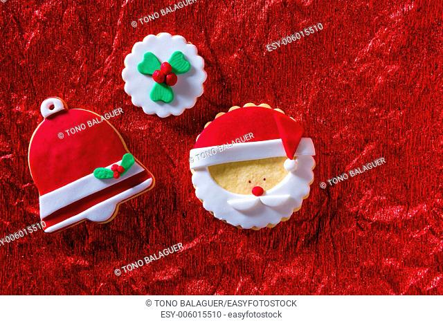 Christmas cookies Santa face and Xmas bell on red background with copy space