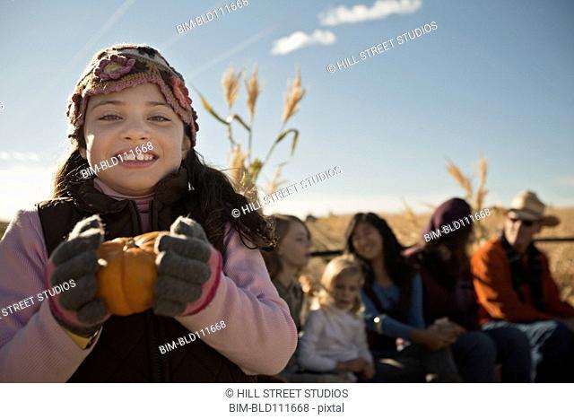Caucasian girl holding pumpkin outdoors