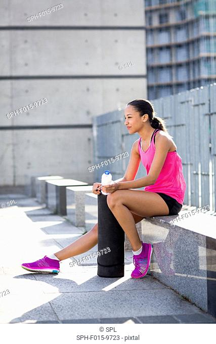 MODEL RELEASED. Young woman sitting on wall with bottle of water, smiling