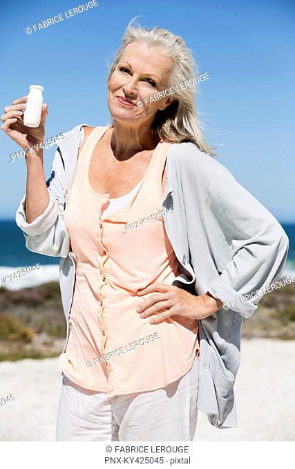 Woman enjoying probiotic drink on the beach