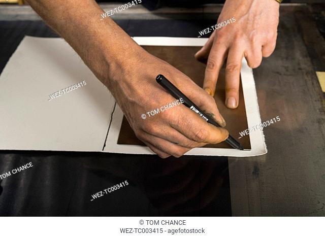 Germany, Bavaria, Mature man drawing outline on paper
