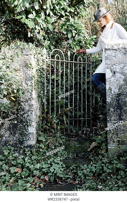 A woman opening a garden gate