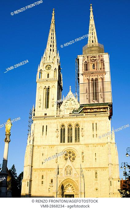 Façade of Zagreb Chatedral in full sunshine with golden statue of Virgin Mary, Zagreb