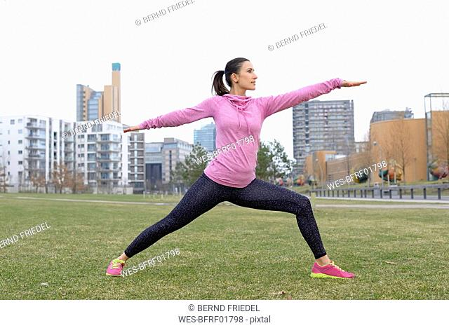 Female athlete exercising on a meadow