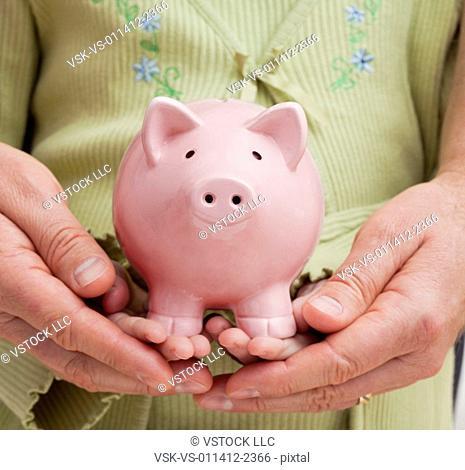 Hands holding piggybank