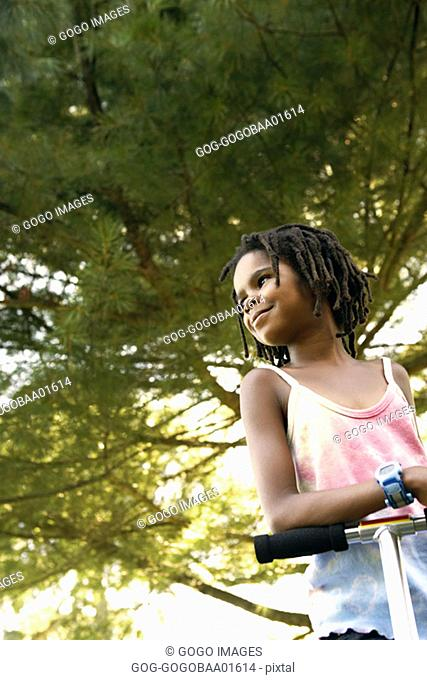 Young African girl riding a scooter