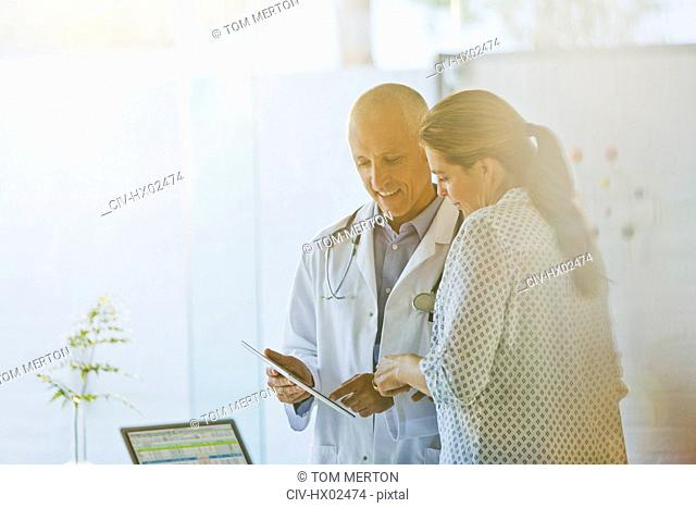 Male doctor showing digital tablet to female patient in doctor's office