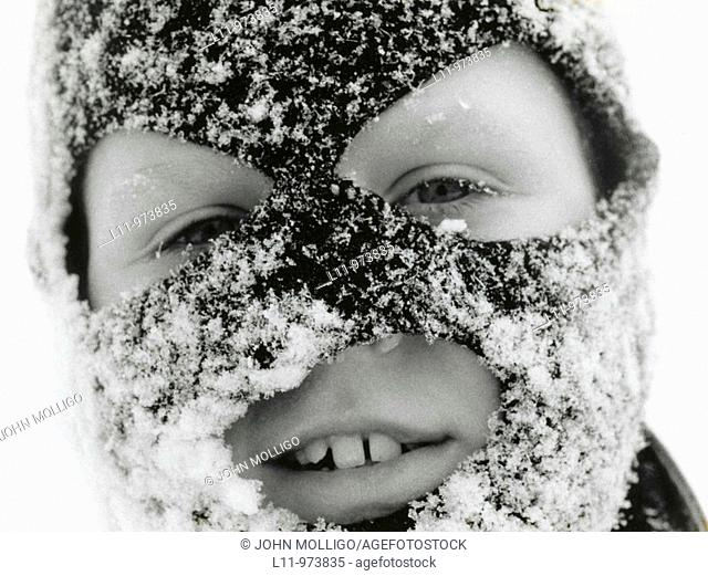 Close-up of boy in ski mask, covered with snow