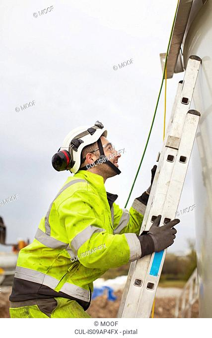 Engineer climbing ladder, working on wind turbine