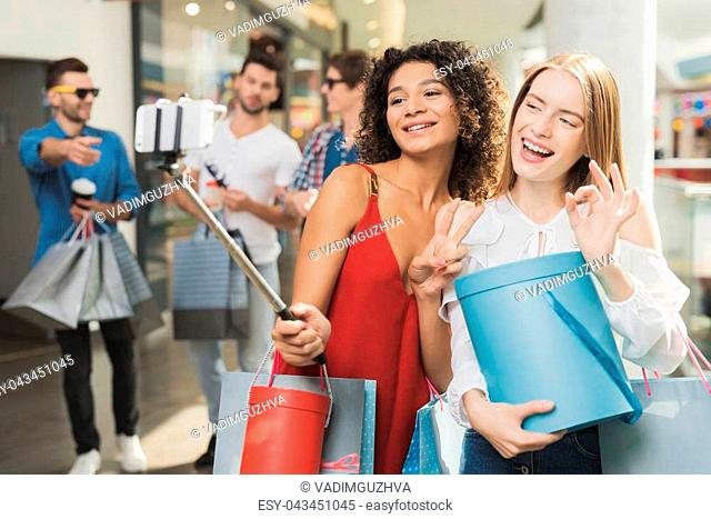 Two beautiful girls have fun in the fitting room. They're shopping on a black Friday. Girls making selfie with purchases in the mall