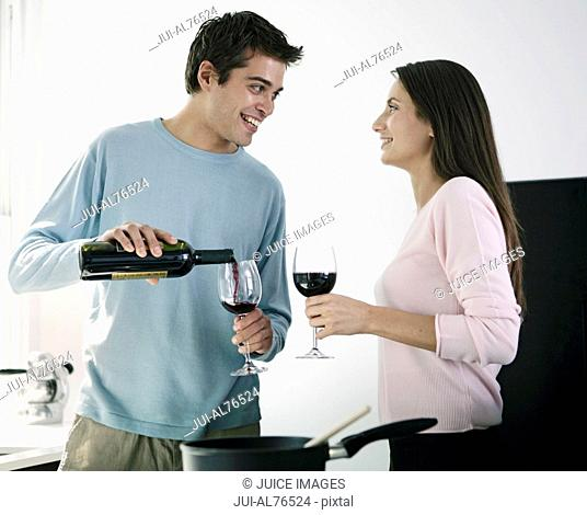 Portrait of a young couple drinking wine in kitchen
