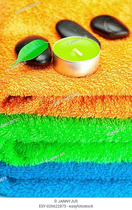 background of the three multi-colored bath towels, black spa stones, green leaves and a candle