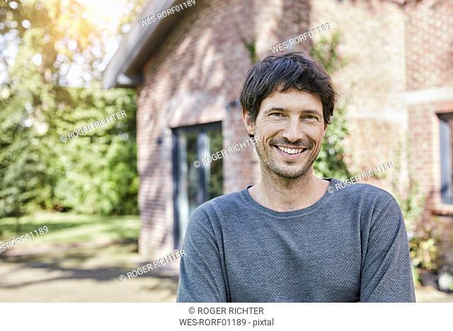 Portrait of smiling man in front of his home