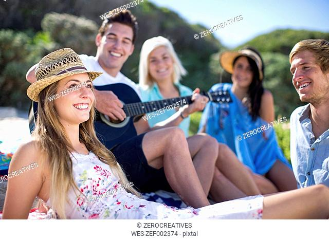 Friends socializing on the beach and playing acoustic guitar