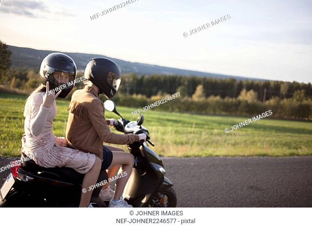 Teenage girls riding on scooter