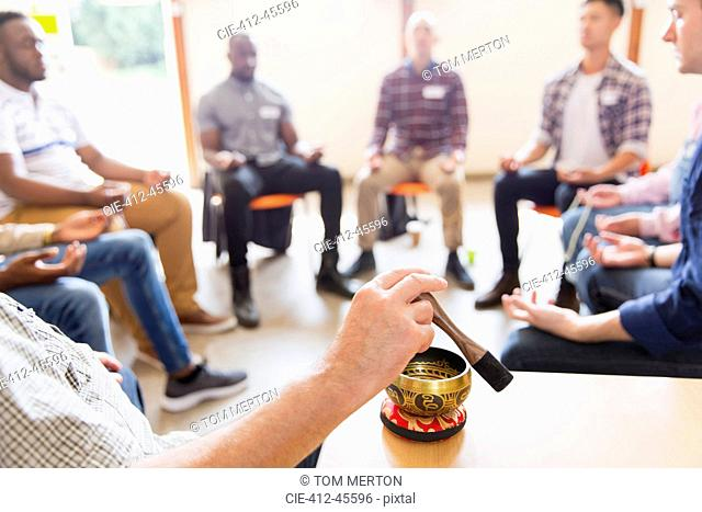 Man using singing bowl in meditation group