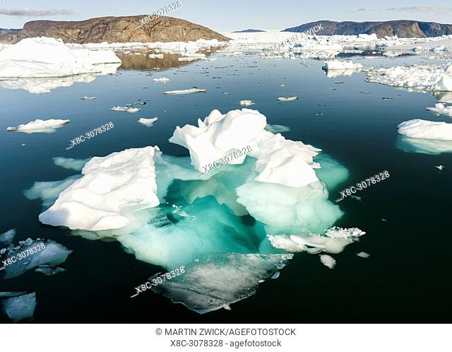 Icebergs in the Uummannaq fjord system in the north of west greenland. Glacier Store Gletscher and the ice cap in the background
