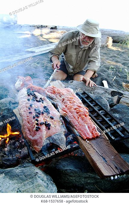 a middle-aged man cooks a salmon over a campfire on Nootka Island, BC, Canada