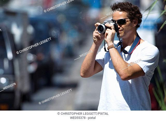 tourist taking snapshot on roadside
