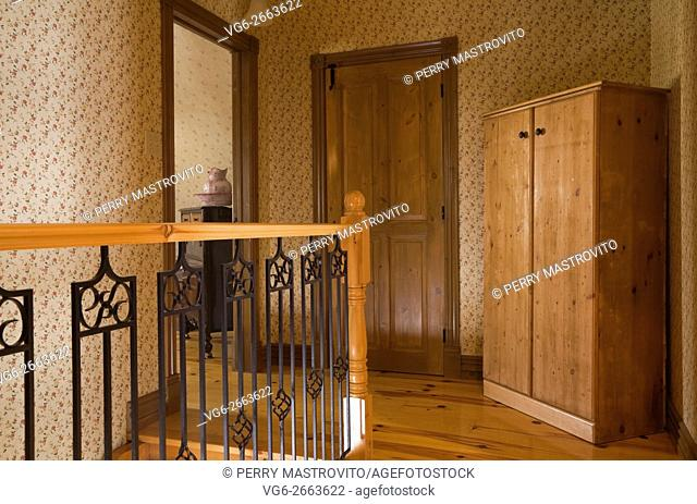 Railing and Armoire on the upstairs floor of a Canadiana cottage style fieldstone residential home built to look old in 2002, Quebec, Canada