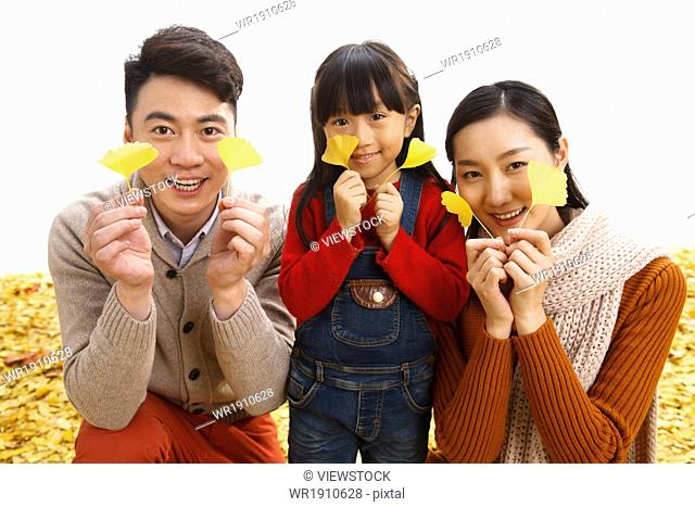 A family of three with ginkgo leaf play