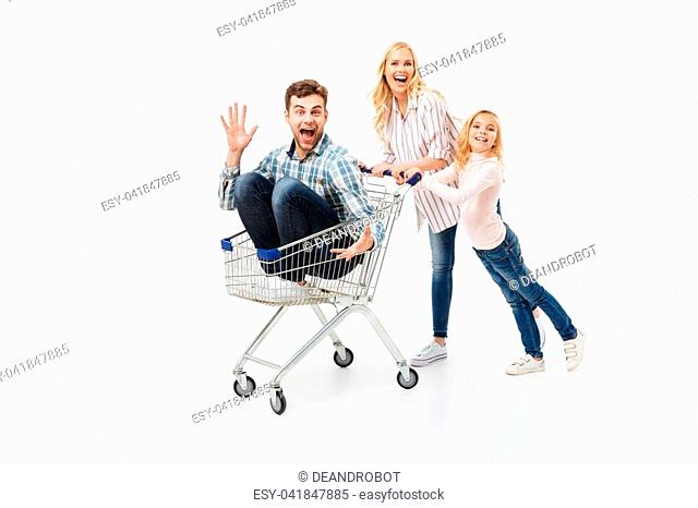 Joyful mother and her daughter giving a ride on a shopping trolley to their father isolated over white background
