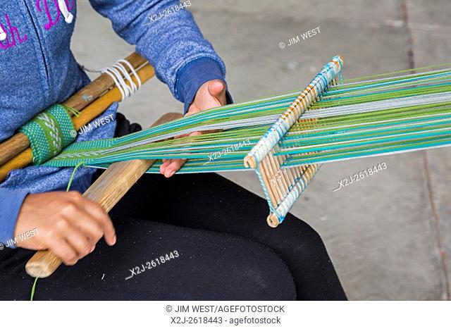 Santo Tomás Jalietza, Oaxaca, Mexico - A woman works on a back strap loom at a weavers cooperative market, where weavers sell their work to tourists