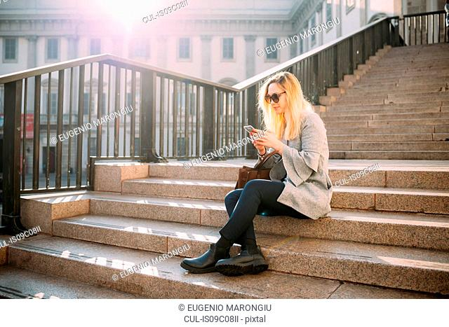Young woman sitting on city stairway looking at smartphone, Milan, Italy
