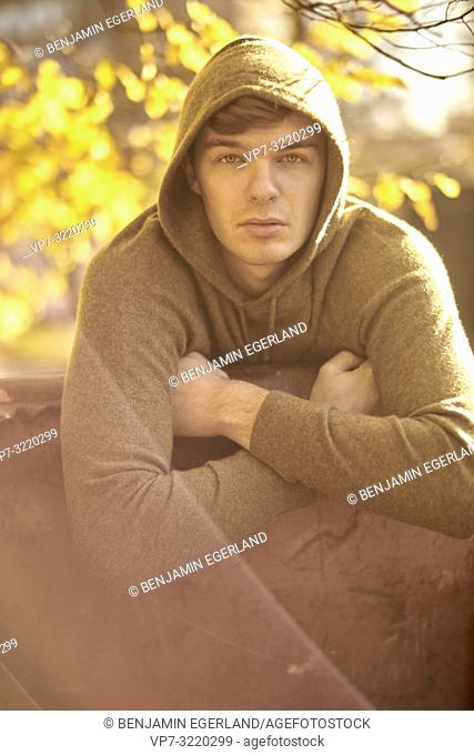 Young man outdoors wearing hoody pullover, autumn, in Munich, Germany