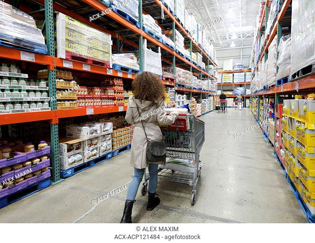 Woman with a shopping cart walking along the aisle of food and groceries section at Costco Wholesale membership warehouse store