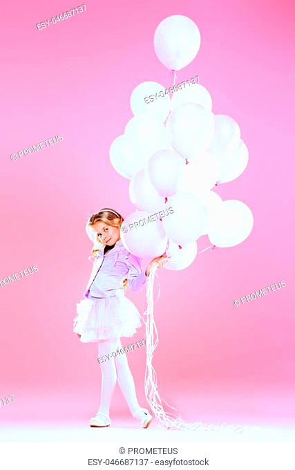 Pretty little girl with beautiful blonde hair alluring with pink balloons over pink background. Little princess with a crown on her head. Kids fashion
