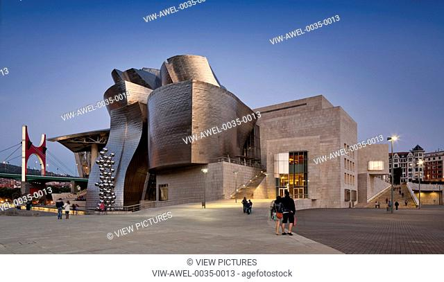 Guggenheim Museum Bilbao, Bilbao, Spain. Architect: Frank Gehry, 1997. General view of riverside elevation at dusk